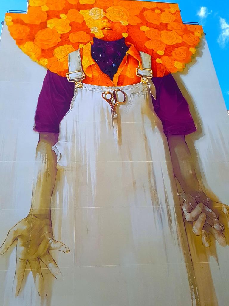 Le street artiste Inti à l'extérieur de la Halle Debourg dans le cadre du festival street art Peinture Fraîche de Lyon