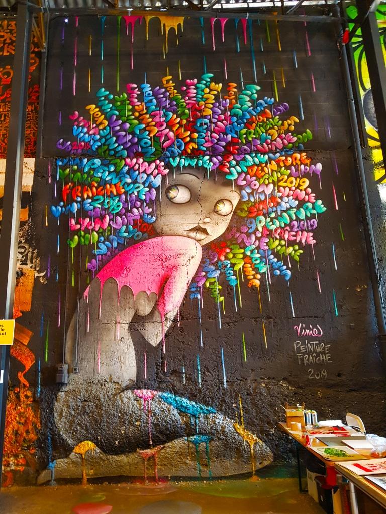 La street artiste française Vinie et son personnage féminin, à mi-chemin entre une poupée et une pin-up, avec sa coiffure afro et à ses dédicaces diverses.